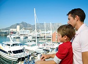 Young boy and his father looking out at boats from Waterfront with Table Mountain in background, Cape Town, Western Cape Province, South Africa