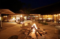 Bonfire in the middle of the lodges with buffet set up in background, Kapama Lodge, Limpopo Province, South Africa