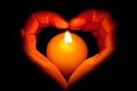 hands as heart through a burning candle
