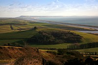 View along Dorset's Jurassic Coast looking towards the Isle of Portland. View showing Chesil Beach with St Catherine's Chapel on a hill above the vill...