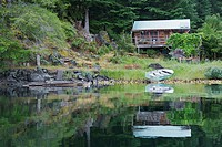 A weekend cabin surrounded by trees on Quadra island, with the lake and a small boat laying on the edge of the lake in front of it