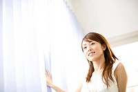 Japanese woman touching a curtain