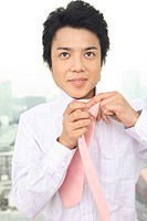 Businessman putting on a tie