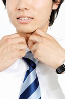 Businessman putting on a necktie