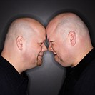 Caucasian bald mid adult identical twin men standing face to face with angry expression