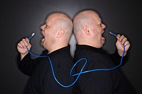 Caucasian bald mid adult identical twin men standing back to back yelling into ethernet cable