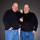 Caucasian bald mid adult identical twin men making obscene gesture at viewer