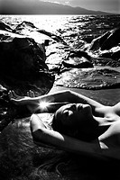 Filipino young nude woman lying on back in water on rocky beach