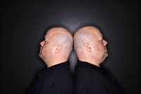 Mid adult identical twin bald men standing back to back.