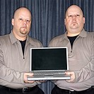 Caucasian bald identical twin men holding a laptop computer and looking at viewer