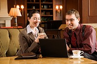 Caucasian mid adult businessman and woman drinking coffee and looking at laptop computer
