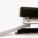 Close up of black stapler on white background stapling paper