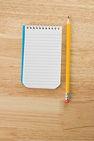 Pencil beside open spiral bound notepad