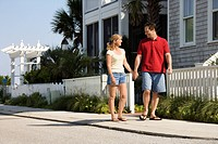 Caucasian mid_adult couple walking on suburban sidewalk holding hands
