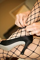 Close up of Caucasian woman in fishnet stockings putting on high heel shoes (thumbnail)