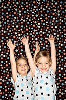 Female children Caucasian twins looking at viewer with arms raised