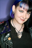 Portrait of Caucasian woman with blue hair and black leather jacket against blue background