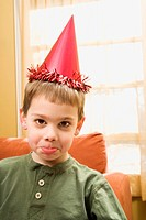 Caucasian boy wearing party hat pouting and looking at viewer (thumbnail)