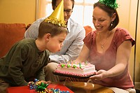 Caucasian boy in party hat blowing out candles on birthday cake with family watching (thumbnail)
