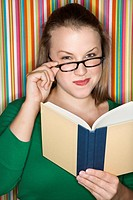 Young Caucasian female adult reading and looking at viewer over glasses
