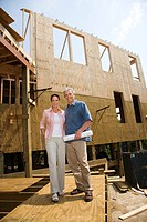 Caucasian mid_adult male holding blue prints with arm around mid_adult female in building construction site