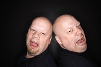 Caucasian bald mid adult identical twin men standing back to back with sad expressions looking at viewer