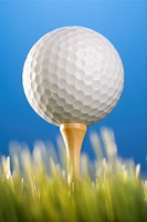Studio shot of a golf ball on a tee in grass
