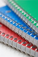 Close up of three spiral bound notebooks stacked up