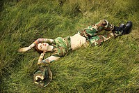 Attractive tattooed Caucasian woman in camouflage lying on grass (thumbnail)