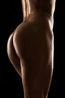 Back view of thighs and buttocks of nude Hispanic mid adult woman glistening with body oil