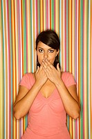 Young adult female Caucasian covering mouth on striped background