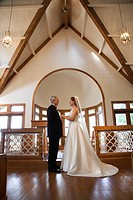 Protrait of bride and groom holding hands at the alter of a church (thumbnail)