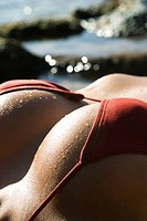 Breast shot of young adult Asian Filipino female lying on beach in bikini.