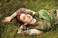 Attractive tattooed Caucasian woman in camouflage lying on grass