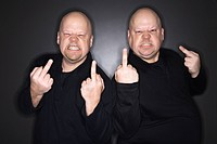 Caucasian bald mid adult identical twin men making obscene gesture at viewer (thumbnail)