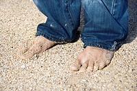 Mid_adult Caucasian male feet in jeans on sandy beach