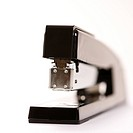 Selective focus of black stapler on white background