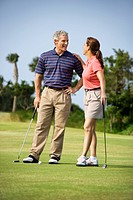 Caucasion mid-adult man and woman standing on golf course talking to each other (thumbnail)