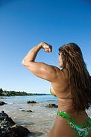 Pretty Caucasian mid adult woman bodybuilder in bikini flexing bicep on beach.