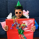 Hispanic boy wearing party hat and sunglasses holding large birthday present smiling and looking at viewer