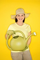 Young adult female Caucasian holding watering can wearing straw hat