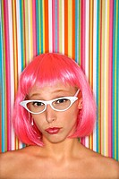 Portrait of attractive Caucasian young adult woman wearing pink wig against striped background looking at viewer