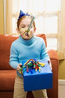 Caucasian girl blowing noisemaker and holding gift