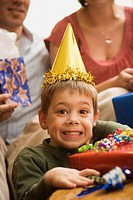 Caucasian boy at birthday party looking at viewer making facial expression