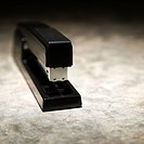 Black stapler on textured background