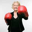 Caucasian senior woman wearing boxing gloves and throwing punch at viewer