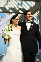 Caucasian mid_adult bride and groom walking together smiling