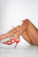 Woman's legs and feet wearing sexy red high heel shoes that lace up to her knees
