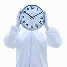 Man in biohazard suit holding clock in front of face standing against white background