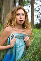 Caucasian young adult woman in lush forest of ferns holding blue sarong over herself